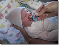 Katie as a beautiful baby girl on the day she was born and me placing a bubba teeth binky in her mouth.